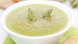 cream soup of asparagus and green peas close-up horizontal -